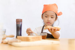 Asian little girl hold the bread and honey dipper stick on white Royalty Free Stock Photo