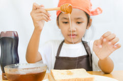 Asian little girl hold the honey dipper to a bread Stock Photo