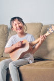 Asian little girl hold an ukulele and smiling Royalty Free Stock Images