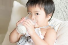 Asian little girl is holding and drinking a glass of milk in living room royalty free stock image
