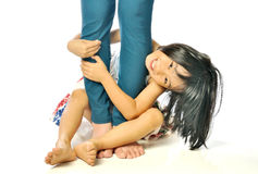 Asian little girl hugging mother's leg and playing Royalty Free Stock Photos