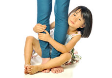 Asian little girl hugging mother's leg and playing Royalty Free Stock Photography