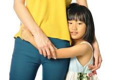 Asian little girl hugging mother's waist Stock Photo