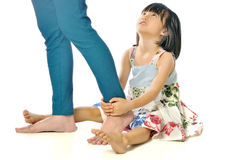 Asian little girl hugging mother's leg and looking up her mother Royalty Free Stock Photos