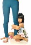 Asian little girl hugging woman's leg and sad Stock Photo