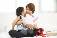Asian little girl kissing her mother stock images