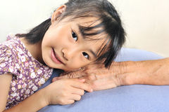 Asian little girl leaning her head on senior hand or her grandmo Stock Photos