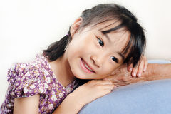 Asian little girl leaning her head on senior hand or her grandmo Royalty Free Stock Image