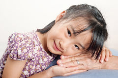 Asian little girl leaning her head on senior hand or her grandmo Royalty Free Stock Photos