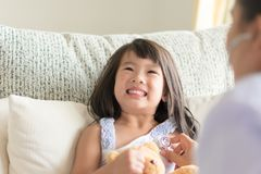 An asian little girl look scared when doctor examining by using stock photos