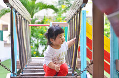 Asian little girl looking for friend playing on playground thail. Asian little girl looking for friend playing on playground bangkok thailand Royalty Free Stock Photography