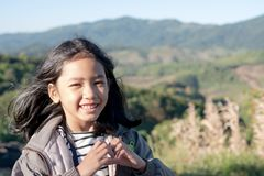 Asian little girl making heart shape. And smiling with traveling on mountains and sunlight with copy space royalty free stock photo