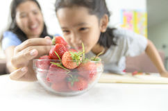 Asian little girl and mother picking straberry in glass bowl, Se Stock Images