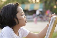Asian little girl painting stock photos