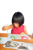 Asian little girl paints pictures with color brush Royalty Free Stock Image