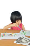 Asian little girl paints pictures with color brush Royalty Free Stock Photo