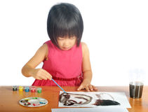 Asian little girl paints pictures with color brush Stock Images