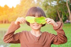 Asian little girl in the park, playing with leaf royalty free stock photography