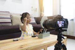 Asian little girl play making a makeup with  recording making video blogger camera for their blog royalty free stock photography