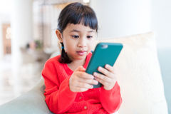 Asian little girl playing cellphone at home royalty free stock images