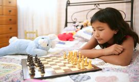 Asian little girl playing chess with teddy rabbit Stock Images