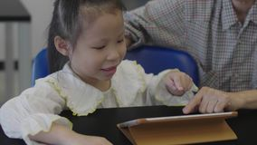 Asian little girl playing on the digital tablet with mother at library. stock video