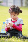 Asian little girl playing on grass Stock Photo