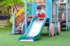 Asian little girl playing slider at playground thailand Stock Images