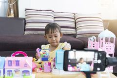 Asian little girl playing toys at home. With recording making video blogger stock images