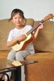 Asian little girl playing ukulele Royalty Free Stock Photo