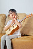 Asian little girl playing ukulele Royalty Free Stock Photo