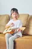 Asian little girl playing ukulele Stock Photography