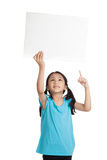Asian little girl point up hold a blank sign Royalty Free Stock Photography