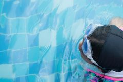 Asian little girl practice swimming for match in swimming pool. Little girl cheerful in this activity.She hard practice swimming b. Ut she very happy Stock Photography