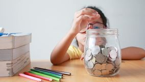 Asian little girl putting the coin into a  clear glass jar with the book on table metaphor saving money for education concept.  stock video