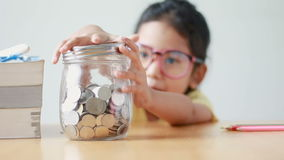 Asian little girl putting the coin into a  clear glass jar on table metaphor saving money concept with sound select focus on jar.  stock footage