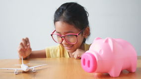 Asian little girl putting the coin into a pink piggy bank with air plane metaphor saving money for travel and transport concept.  stock video