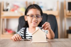 Asian little girl in putting coin in to house piggy bank shallow Royalty Free Stock Photography