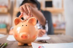 Asian little girl in putting coin in to piggy bank shallow depth Stock Photo