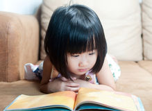 Asian little girl reading book Royalty Free Stock Photos