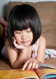 Asian little girl reading book Royalty Free Stock Photo
