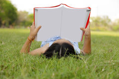 Girl reading book in the park Stock Images