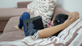 Asian little girl relax lying on a sofa and using tablet. Asian little girl relax lying on the sofa and using tablet stock video