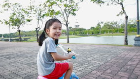 Asian little girl riding a bicycle in public park with camera follower stock footage
