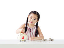 Asian little girl saving money in a piggy bank. Isolated on white background Stock Images