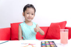 Asian little girl showing thumb up and play water color Stock Image
