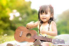 Asian little girl sitting on grass and play ukulele in garden Royalty Free Stock Photos