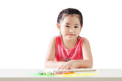 Asian little girl is sitting at the table. Isolated over white Stock Photography