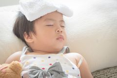 Asian little girl sleep and sick on sofa with cooler gel on her royalty free stock photography