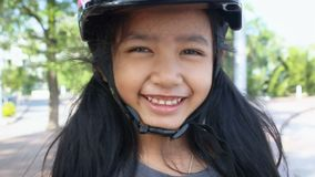 Asian little girl Smile with happiness wearing sport safety helmet stock video